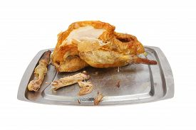 picture of guinea fowl  - Roast partly carved Guinea fowl on a carving dish - JPG