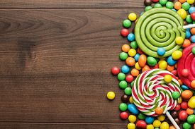 foto of lollipops  - different colorful sweets and lollipops on the wooden table - JPG