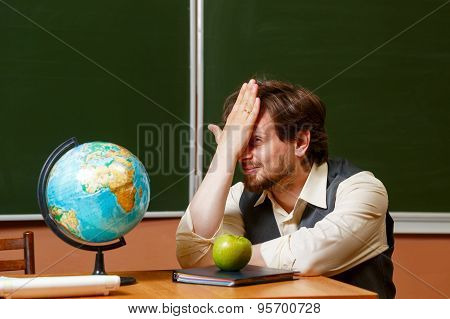 Geography Teacher Sits In Front Of A Globe.