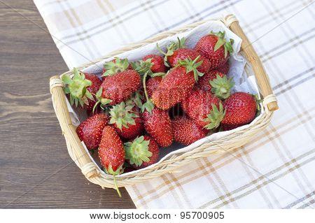 Fresh strawberries with green tails wickerwork basket with white napkin
