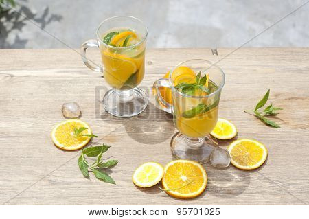 Orange fresh drinks with ice and mint on wooden table