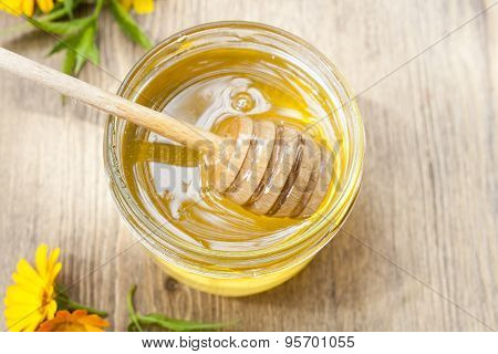 Linden honey in jar and calendula blossoms on wooden table
