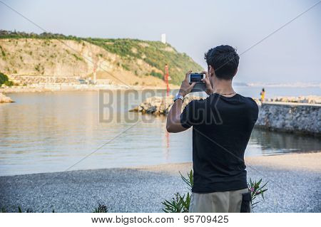 Rear View of Young Man Taking Photos at the Beach