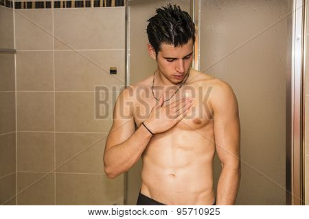 Muscular fit young man applying ointment to his chest