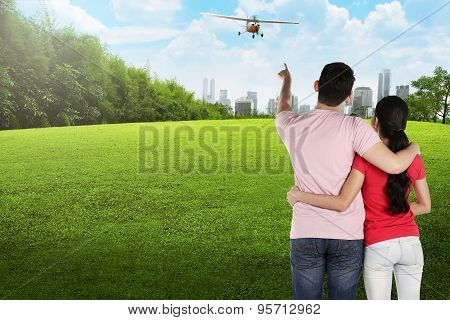 Asian Couple Pointing Propeller Plane
