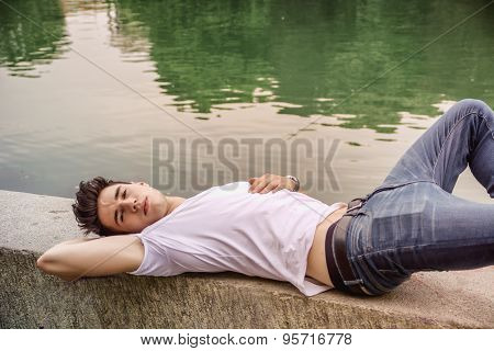 Handsome young man on a lake's shore or river banks