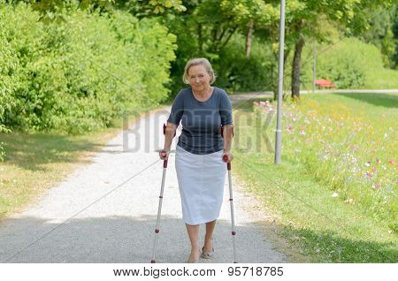 Elderly Lady Walking In The Country On Crutches