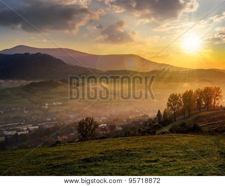 Meadow Near Village In Autumn Mountains At Sunset