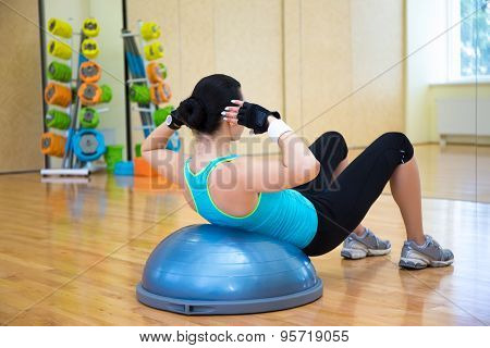 Slim Woman Working Out With Bosu Ball In Gym