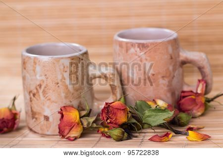 vintage mags of roses tea and dry rosebuds on wooden background