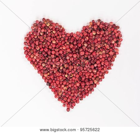 isolated heart laid out from the red peppercorns. View from above.