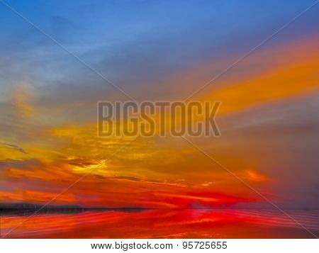 Sunset Sky Of Deep Multiple Colors Scaterred Rays Of Lights And Its Reflection On Water.