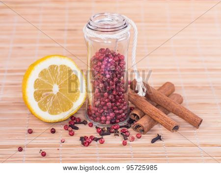 red peppercorn in glass and spice on wooden background.