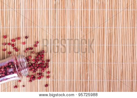 red peppercorns in glass on wooden background. View from above.