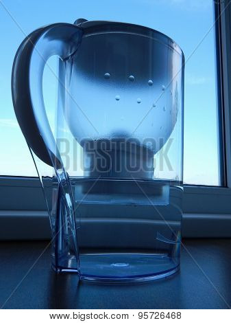 Home water filter with purified water at windowsill