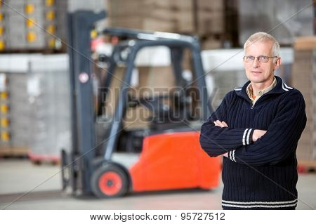 Portrait of confident supervisor with arms crossed standing at distribution warehouse