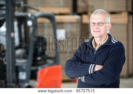 Portrait of confident male worker standing arms crossed at distribution warehouse