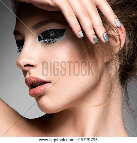 Beautiful girl with bright creative fashion makeup and Grey nail polish. Art beauty design.