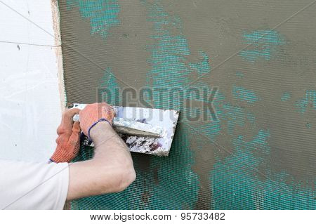 Applying Putty To The  Wall Using A Spatula