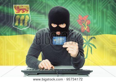 Hacker Holding Credit Card And Canadian Province Flag On Background - Saskatchewan