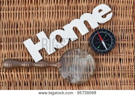 Wood Sign Home, Compass And Vintage Magnifier On Wicker Background