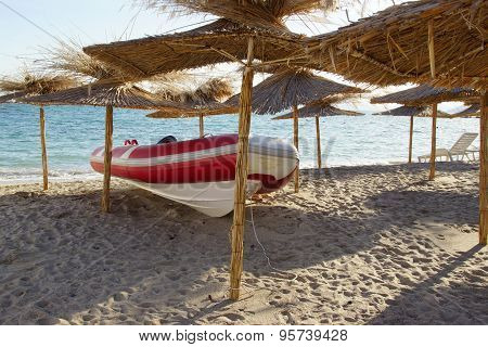 Red White Speedboat Under Beach Umbrella