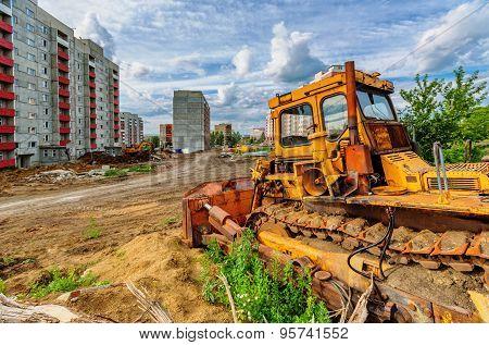 Bulldozer And Houses Beneath Cloudy Sky