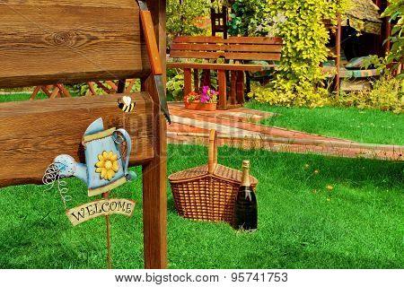Outdoor Wooden Furniture Picnic Hamper Basket Champagne Wine Bottle Bbq Grill Tools Empty Wood Signboard Sign Garden Plants Trees In The Background