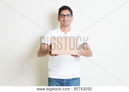 Courier delivery service concept. Indian man sending a brown box, standing on plain background with shadow. Asian handsome guy model.