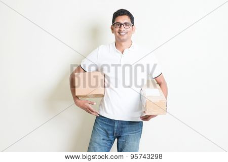 Courier delivery service concept. Happy Indian man received brown boxes, standing on plain background with shadow. Asian handsome guy model.