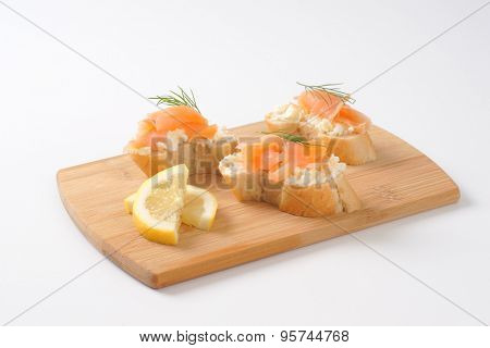 smoked salmon canapes on wooden cutting board
