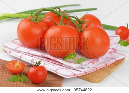 close up of fresh tomatoes on checkered dishtowel