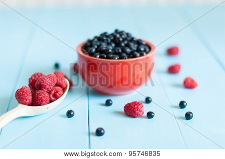Blueberry antioxidant organic superfood in a bowl and ripe sweet raspberries at spoon. Concept for h