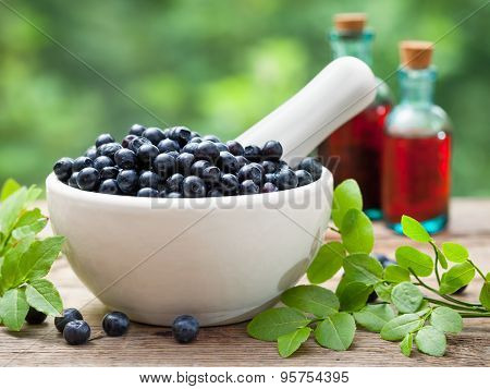 Mortar With  Blueberries And Bottles Of Tincture Or Cosmetic Product On Background.