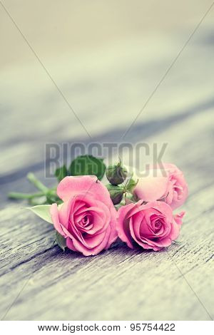 Vintage Stylized Photo Of Roses Bunch On Old Wooden Background.