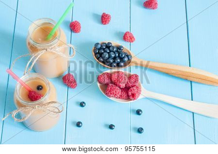 Jars of homemade peach jam or preserves and spoon with fresh rastberries, blueberries at blue wooden
