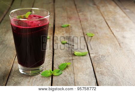 Glass of beet juice on wooden background