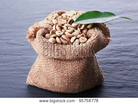 Burlap bag of green coffee beans on wooden table, closeup