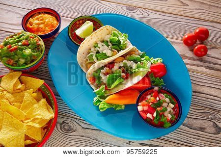Fish tacos mexican food with guacamole nachos and chili pepper sauce