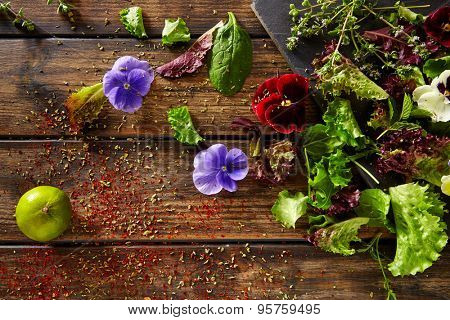 Fresh salad ingredients lettuce flowers spinach on rustic wood
