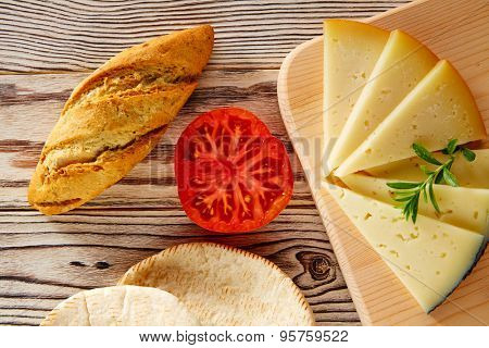 Mediterranean food bread loaf tomatoes and cheese slices on rustic wood