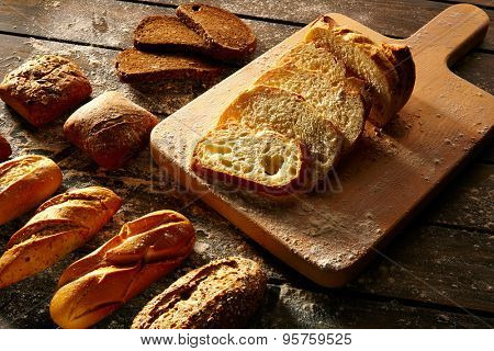 Bread varied loafs sliced on wood board in rustic wood table