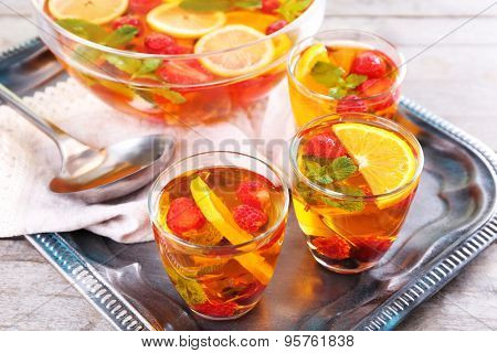 Fruity punch in glassware on metal tray, closeup