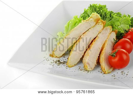 Slices of  chicken fillet with cherry tomato and lettuce on plate isolated on white