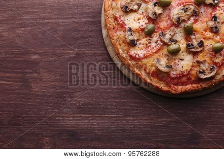 Tasty pizza with vegetables on wooden background