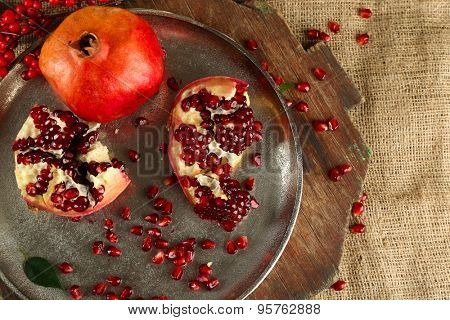 Pomegranate seeds on metal tray and sackcloth, closeup