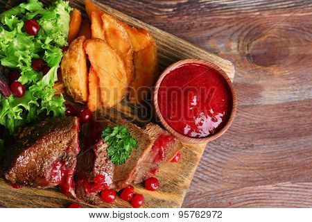 Beef with cranberry sauce, roasted potato slices on cutting board, on wooden background