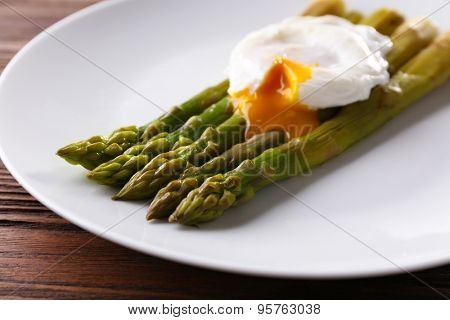 Roasted asparagus with poached egg on plate on table close up