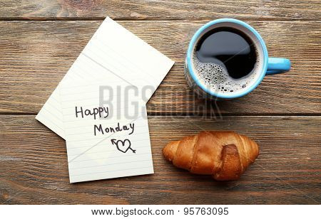 Cup of coffee with fresh croissant and Happy Monday massage on wooden table, top view