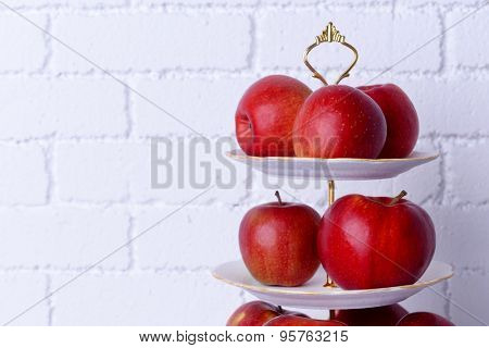 Tasty ripe apples on serving tray on brick wall background